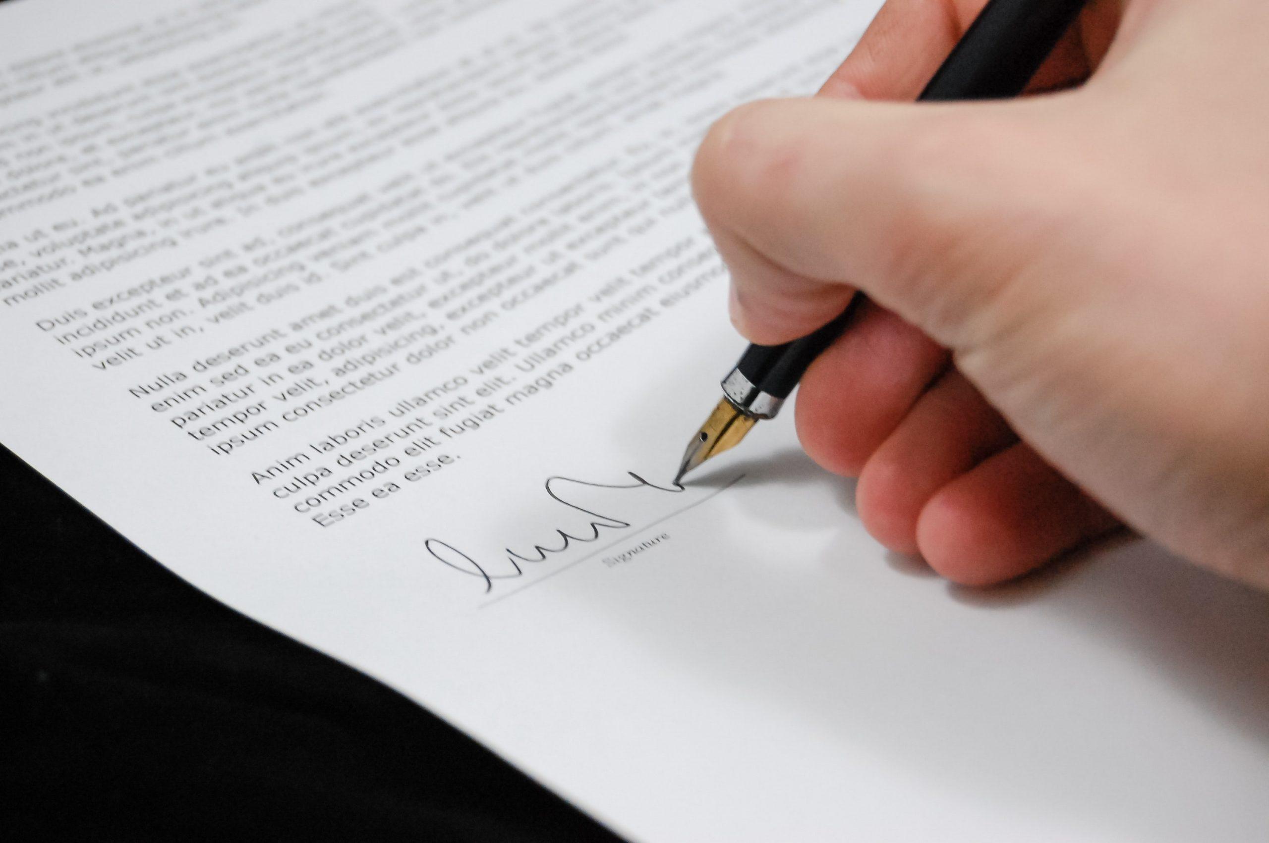 Someone signing paper