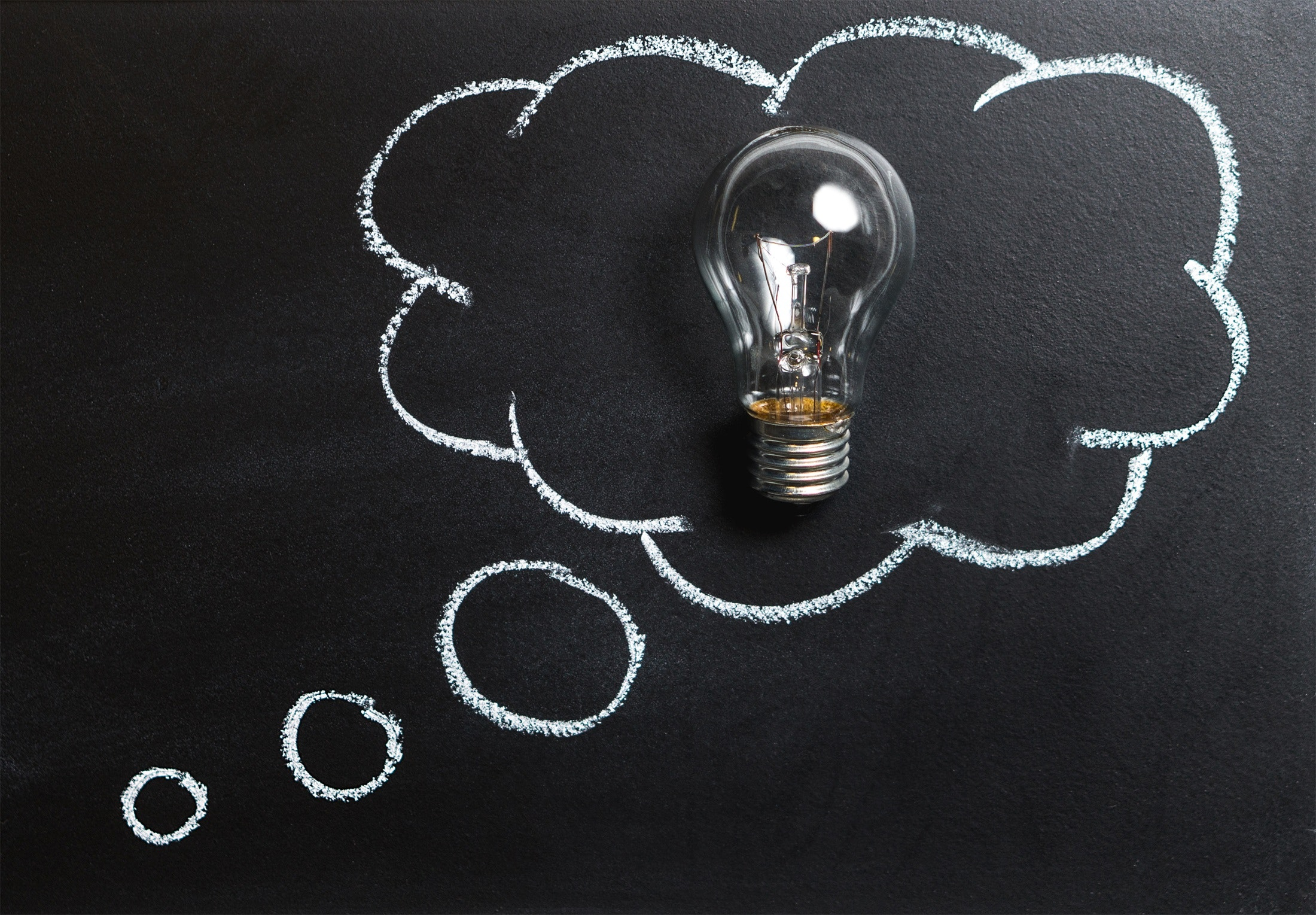 Thought bubble with a lightbulb inside on a blackboard